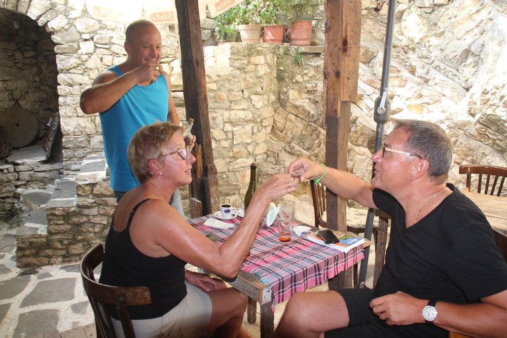 Ilia Theodhori serverer raki til Sylvie Vanroelen og Rudi Claerhout - og skåler gjerne med gjestene. Foto: Odd Roar Lange