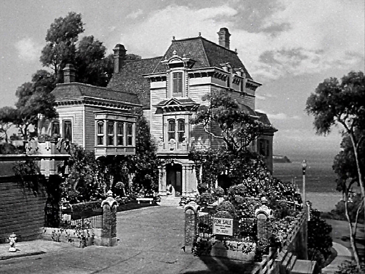 This is an overall view of the house, seen early in the movie.   But this is a painting!   It's geographically consistent with the Julius' Castle location, even down to the glimpse of Alcatraz Island in the Bay.