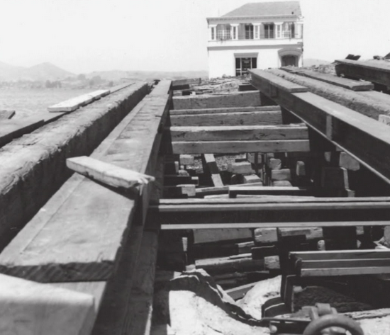A close-up shot of the track to the barge shows the amount of work and detail that went into building the ramp to slide the buildings from land to barge. A similar ramp for unloading was later built on the other side of the bay. With one of the halves of the Moffitt Mansion in the distance, it is easy to appreciate the immense size and scope of the project.