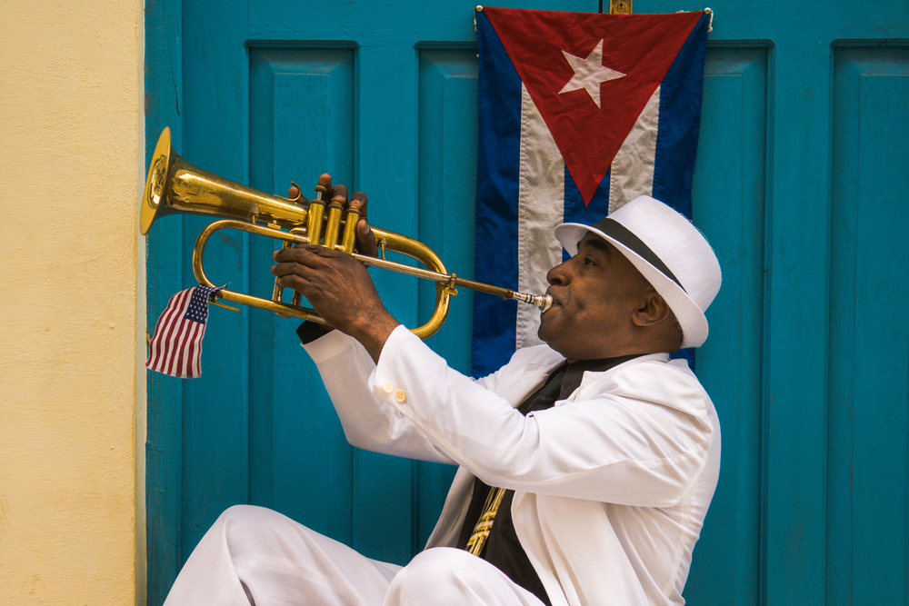 ISO 200 / 32mm / f2.8 / 1/800sec -   Trumpet player on the streets of old Havana. Notice the American flag?
