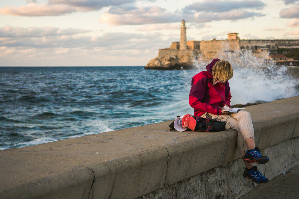 ISO 200 / 45mm / f2.8 / 1/500sec -   The Malecon is a roadway-seawal along the coast of Havana. Michael and I were walking along the Malecon when I spotted this lady reading. You can see the fortress and lighthouse overlooking the city behind her.