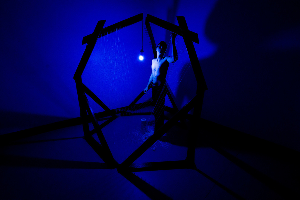 Shadow Dance, 2016, center structure 7.5' x 7.5' x 7.5' with 2.5' additional space around for shadows, human, wood, bolts, nails, latex paint, chenille thread, blue florescent light, electrical tape