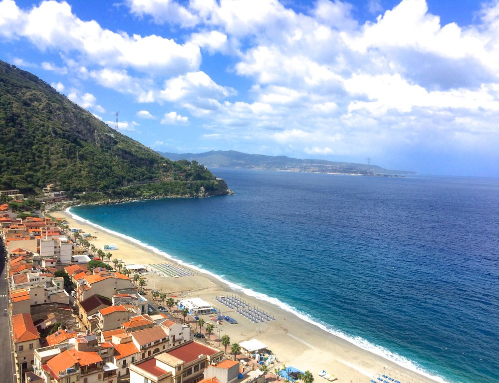 Scilla's beautiful mermaid beach with a view of Sicily in the distance.