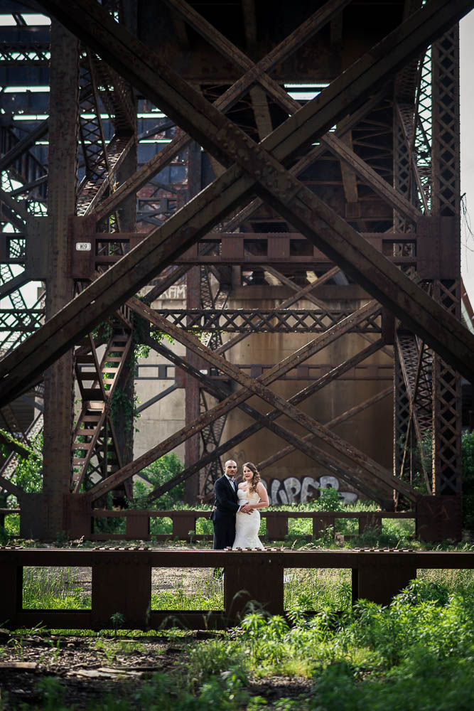 A portrait of a bride and groom under train tracks in downtown St. Louis, Missouri.