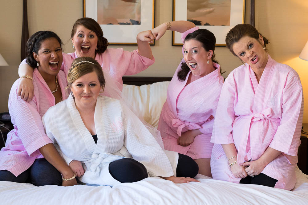 A bride and her bridesmaid's pose for a silly portrait in their hotel room.