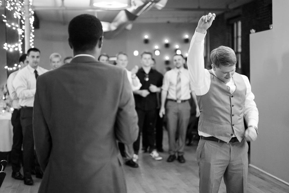 A black and white photograph of the garter toss during a reception at Jim Edmonds Space 15.