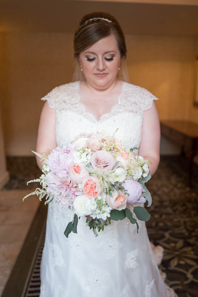 A natural light portrait of a bride and her bouquet moments before her wedding.