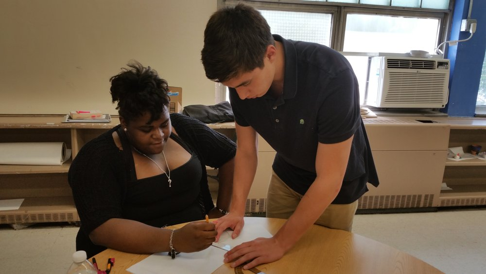 Max Jacobs, summer intern and course teacher's assistant, helping Dreamer Tatyana Dennis with her coursework.