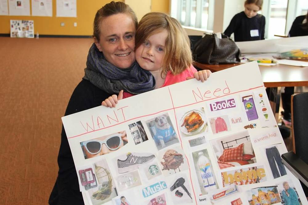 "A mom and daughter share their ""Needs vs. Wants"" poster at Make It Count!"