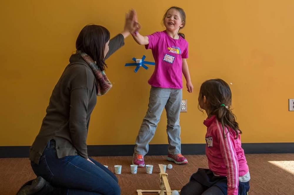 A mom and daughter slap-five after getting their ping pong ball launcher to work at our STEM program Build Bridges! Photo by Diane Hammer