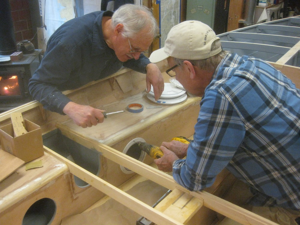 "Rick drills fastener holes for the inspection ports on the 14'6"" GANNET dinghy's side benches. These watertight compartments will provide flotation in the event of swamping. Bob looks ready to install some screws."