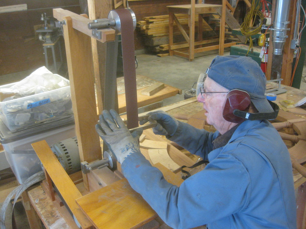 "Jim is using his shop-built ribbon sander to clean up the GANNET's rudder hardware castings. The sander uses 2"" x 72"" belts, and is powered by a two speed washing machine motor. It's perfect for jobs like this. Jim is currently building one for the GHB."