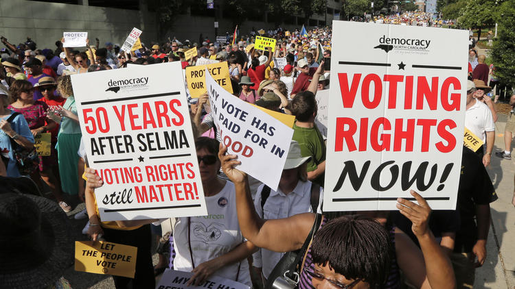 Demonstrators march through the streets of Winston-Salem, N.C. on July 13, 2015, after the beginning of a federal voting rights trial challenging a 2013 state law. (Chuck Burton / Associated Press)