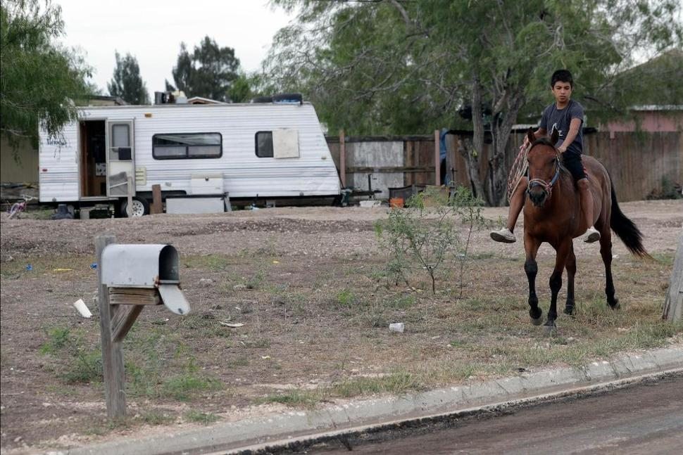 In this Wednesday, July 12, 2017 photo, a boy rides a horse through Indian Hills East colonia near Alamo, Texas. Texas has more than 2,300 of these communities, known as colonias, that have sprung up around towns and provide shelter to Hispanic immigrant families, most of whom are in the U.S. legally, but others not. (AP Photo/Eric Gay) THE ASSOCIATED PRESS