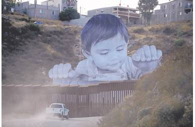 GREGORY BULL / ASSOCIATED PRESS A U. S. Border Patrol vehicle drives in front of the huge photo of a toddler in Tecate, Mexico, just beyond a border barrier.