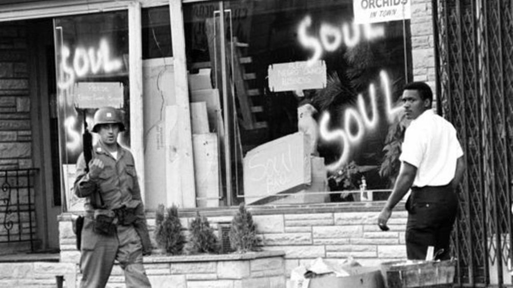 FILE - In this July 15, 1967 file photo a National Guard officer passes the smashed window of a black-owned flower shop in riot-torn Newark, N.J. The last surviving member of the Kerner Commission says he remains haunted that the panel's recommendations on US race relation and poverty were never adopted, but he is hopeful they will be one day. Former U.S. Sen. Fred Harris says 50 years after working on a report to examine the causes of the late 1960s race riots he strongly feels that poverty and structural racism still enflames racial tensions even as the United States becomes more diverse. AP Photo,File)