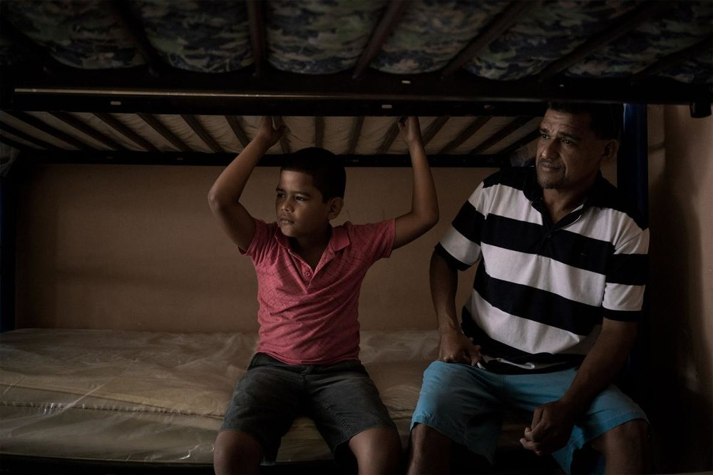 Luis German Ruiz and his son, Luis Fernando Ruiz, sit on their bed at the Casa del Migrante Frontera Digna. They left Honduras to escape the violence that had already taken three family.  PHOTOGRAPH BY TAMARA MERINO, NATIONAL GEOGRAPHIC