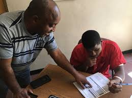 Pastor Kenneth Glasgow helps Spencer Trawick, an inmate at the Dothan City Jail in Dothan, Ala., fill out a voter registration form in June 2017. CONNOR SHEETS/AL.COM