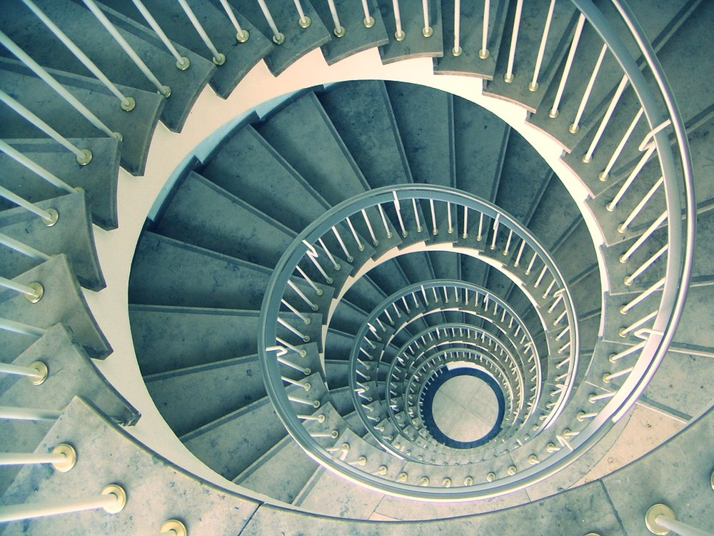 This staircase is a good illustration of a spiral curriculum. As a person walks up, the circular design causes them to revisit the same part of the structure that they had previously been to, but each time they are one level higher.