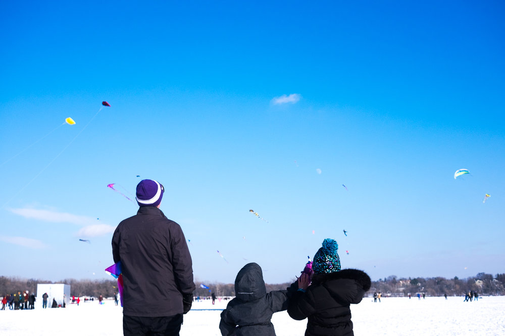 Father and daughters at the Lake Harriet Winter Kite Festival, Minneapolis, Minnesota