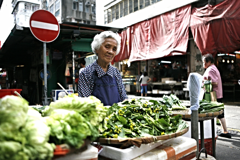 Elderly lady selling produce at a streetside market