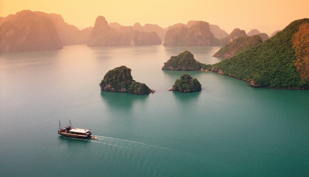 The karsts and a passing junk boat in Ha Long Bay - photo credit Pintrest