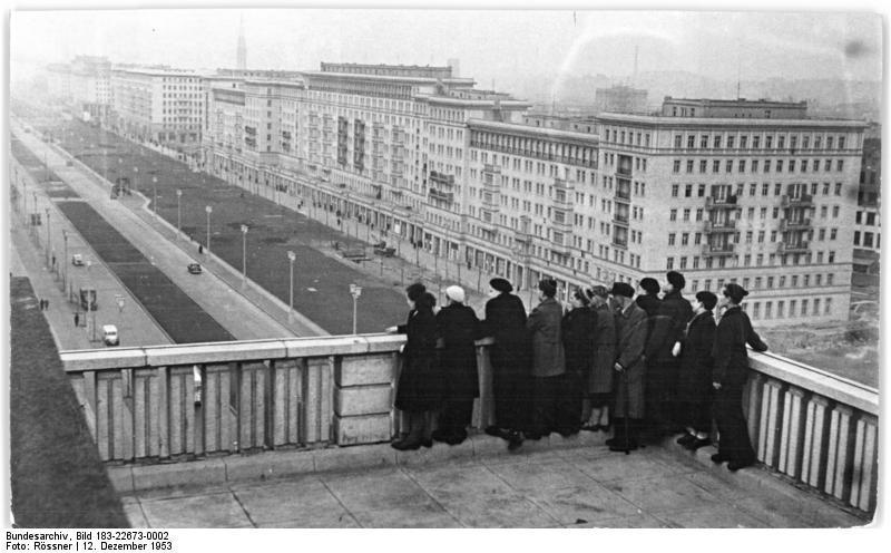 """Estudiantes visitan un congreso de astronomía en Berlín Oriental y miran desde lo alto la avenida """"Stalinallee"""" (hoy Frankfurter Allee/Karl-Marx-Allee), 12 de diciembre de 1953."""