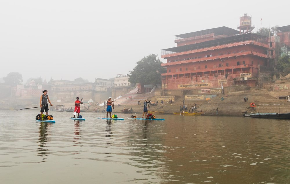 The team paddle past Varanasi
