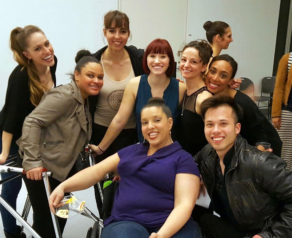 Seven female dancers and one male dancer in street clothes clothes smiling for group photo. Some are seated or standing using wheelchairs or walkers
