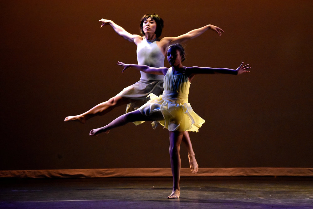 Female dancer in a light grey dress jumps behind a girl in a yellow dress. Both have their legs and arms extended out in unison.