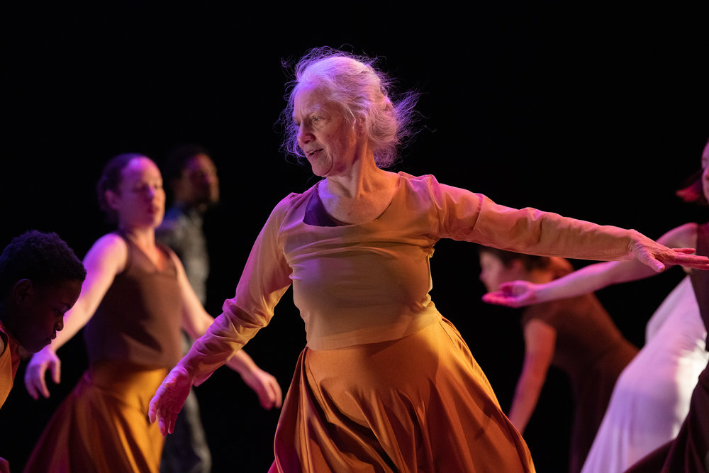 On the Way to School:   Sara Schwabacher dressed in a gold and beige top and skirt turning with her arms out to the side. Other dancers appear in the background in similar turns. Photo: Steven Pisano