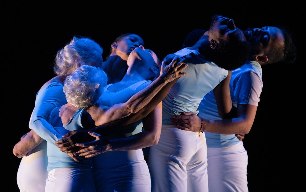 Stillpoint:   Eight dancers embrace in a small group as they all circle their trunks and heads in the same direction while supporting and holding each other. Dancers are dressed in white pants and light blue tops, while dark blue lighting casts a glow. Photo: Steven Pisano