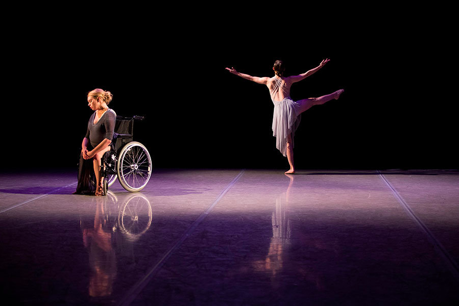 Dancer Madison Ferris sits in a wheelchair and dancer Madeline Charles stands in the back with her back to the audience and one leg and both arms extended up.