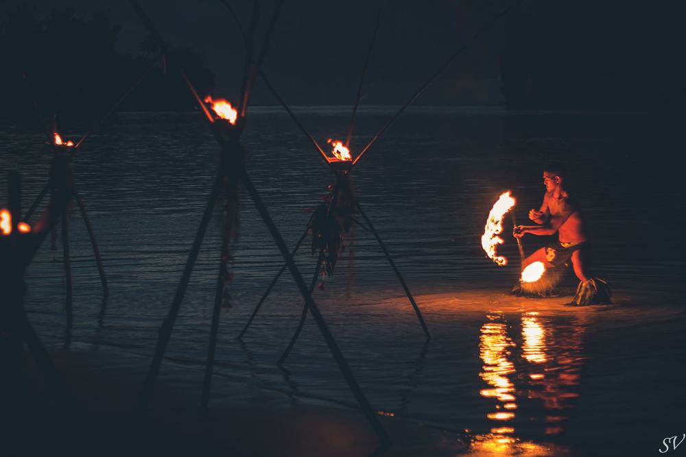 Fire dancer into the lagoon during a wedding