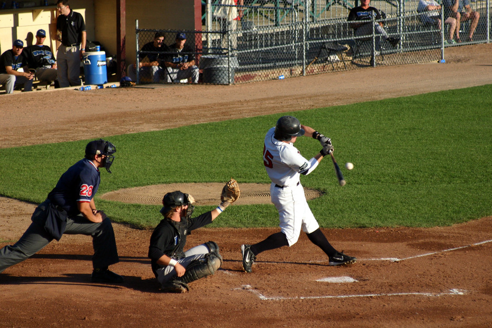 baseball game with batter swinging at a pitch.