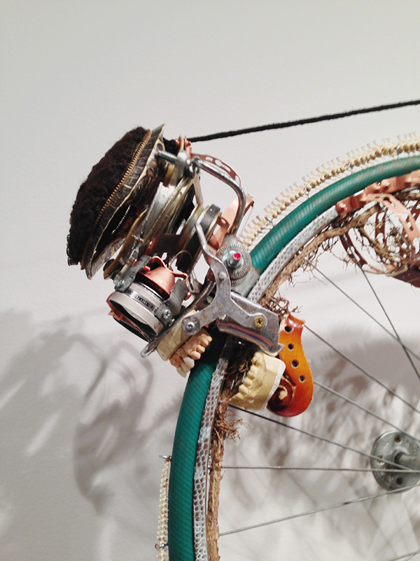 5 Lorna Williams-Ouroboros-2013-hair, plumbing hardware, violin parts, photography lenses, snake vertebrae, bike wheel, hose, ukulele neck, bike chain, plaster teeth, bike seat, speaker, snake shedding, root, rope, cement-88x60x13-detail.jpg