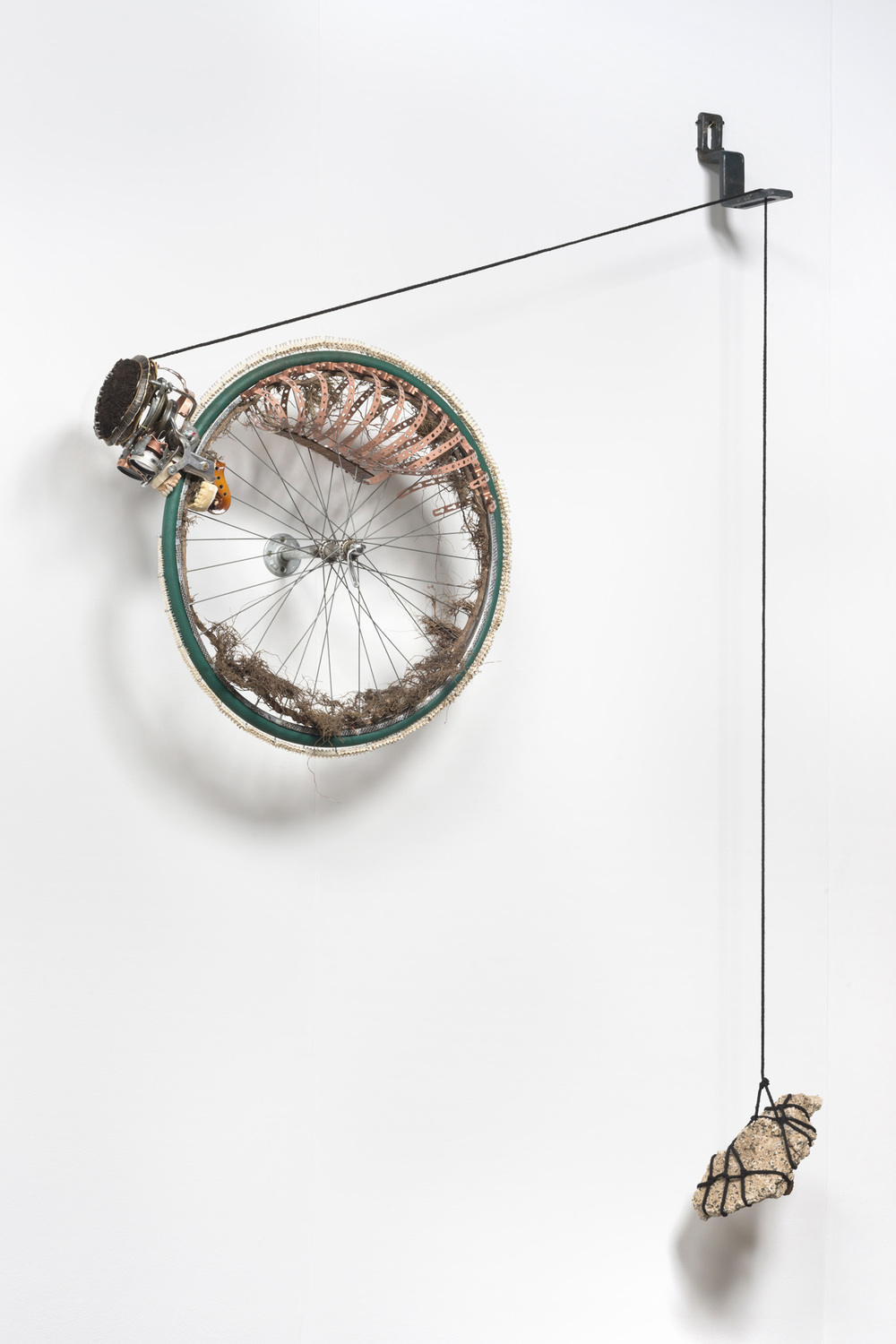 Lorna Williams-Ouroboros-2013-hair, plumbing hardware, violin parts, photography lenses, snake vertebrae, bike wheel, hose, ukulele neck, bike chain, plaster teeth, bike seat, speaker, snake shedding, root, rope, cement-88x60x13.jpg