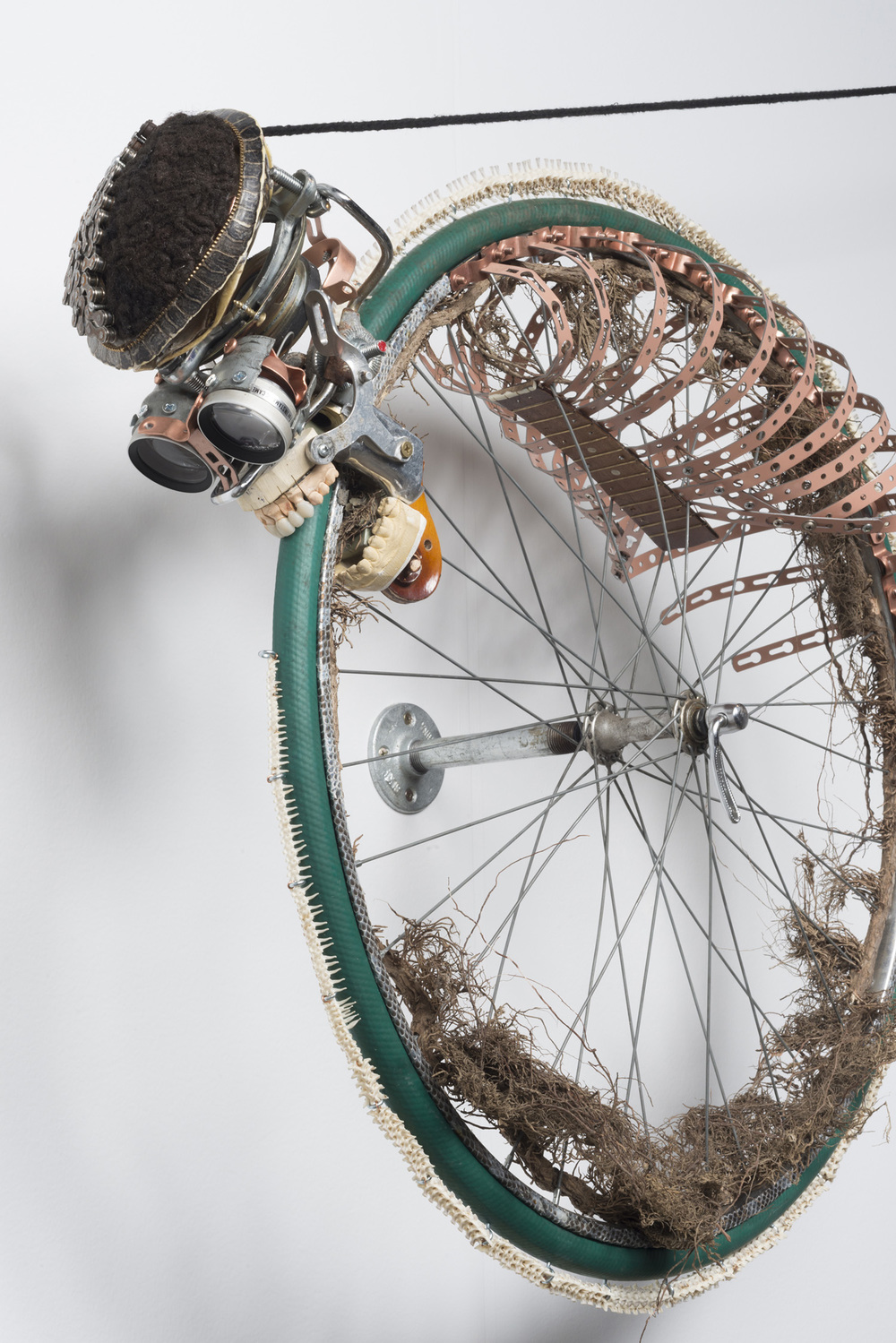 Lorna Williams-Ouroboros-2013-hair, plumbing hardware, violin parts, photography lenses, snake vertebrae, bike wheel, hose, ukulele neck, bike chain, plaster teeth, bike seat, speaker, snake shedding, root, rope, cement-88x60x13-detail-1.jpg