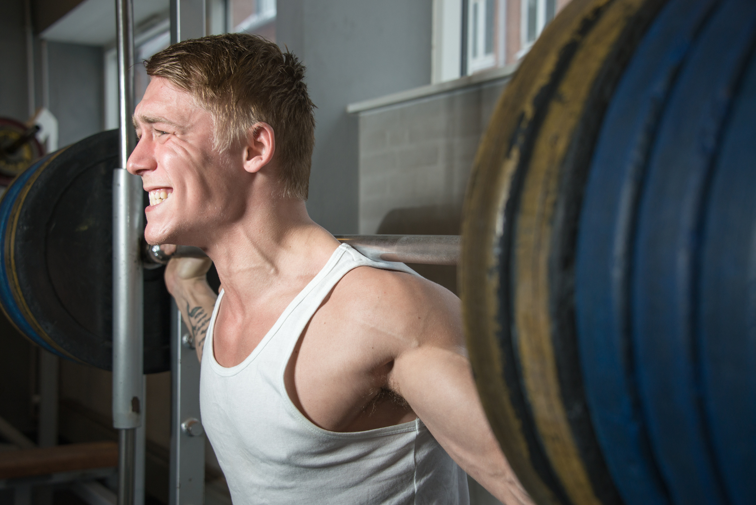 Young bodybuilder training heavy weights in smith machine