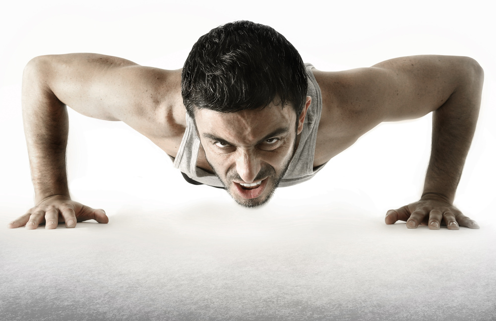 attractive young sport man training his body doing push up exercise showing suffering and sacrifice face expression isolated on white background