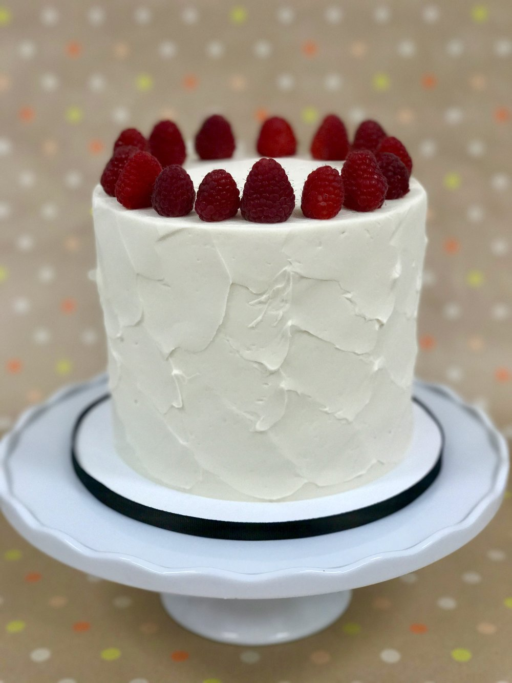 White Chocolate Raspberry - Cake: White ChocolateFilling: White Chocolate Raspberry Buttercream and Fresh RaspberriesFrosting: Vanilla Swiss Meringue Buttercream and Fresh Raspberries