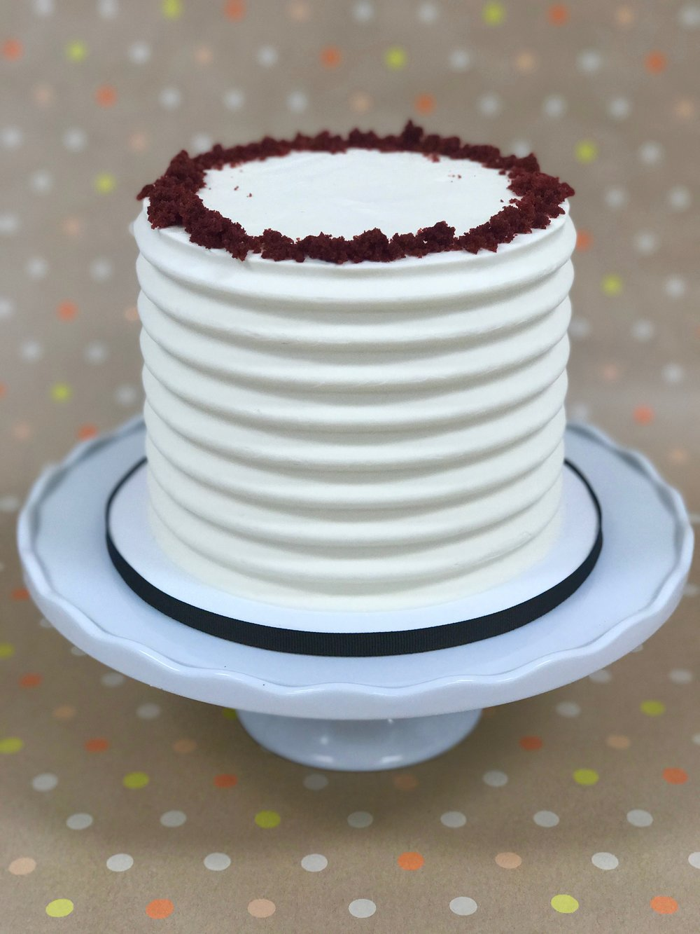 Red Velvet - Cake: Red VelvetFilling: Vanilla Cream CheeseFrosting: Vanilla Swiss Meringue Buttercream and Red Velvet Cake Crumbs