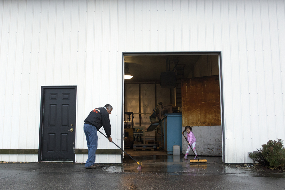"Ignacio ""Nacho"" Jurado, 57, left, and Annalee, 5, right, clean the water out of the warehouse at Uncle John's Cider Mill. The children have all grown up around work. By the age of five, it is common for them to get curious and mimic what the rest of the family is doing. Ignacio says that he hopes his children will grow up and not be afraid of hard work."