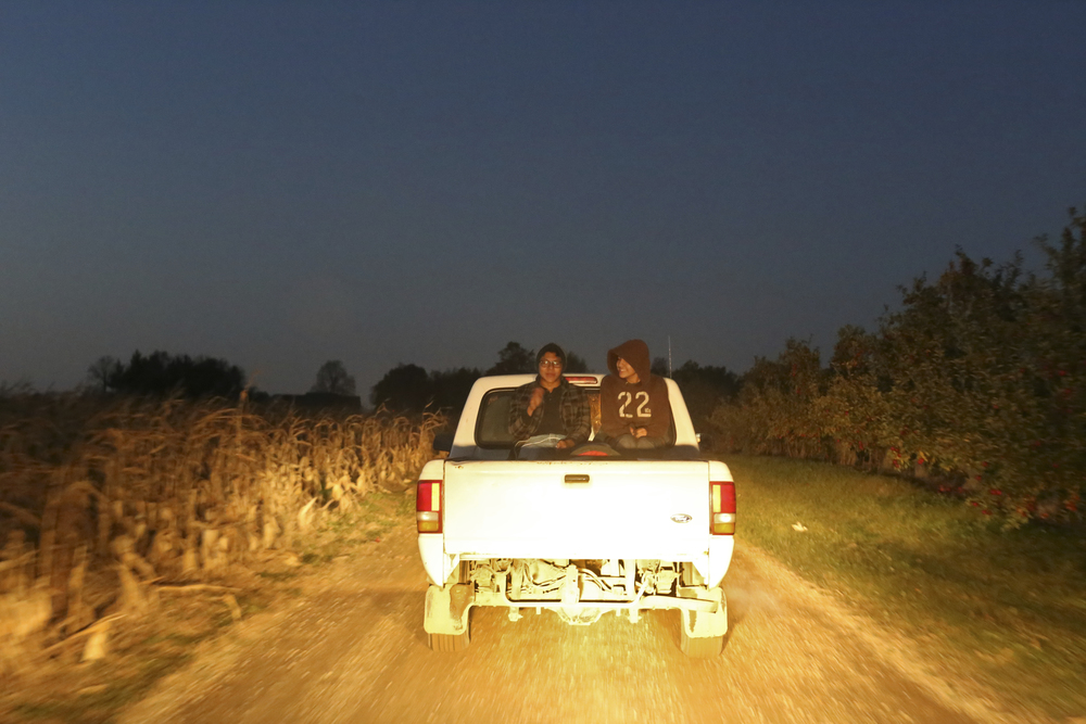 Ignacio Jurado, 17, and his brother Leo, 13, ride in the back of a truck to begin another night of work at Uncle John's Cider Mill.