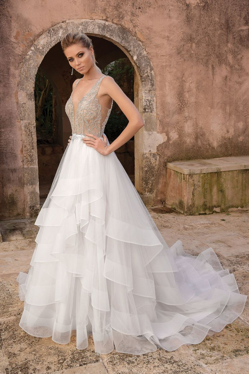 Style: 88059  Feel like a princess on your wedding day wearing this couture inspired beaded ball gown. This gown has an allover illusion beaded bodice that leads into a natural waistline. Features a plunging neckline, ruffled skirt with horsehair trim and a low V-back.