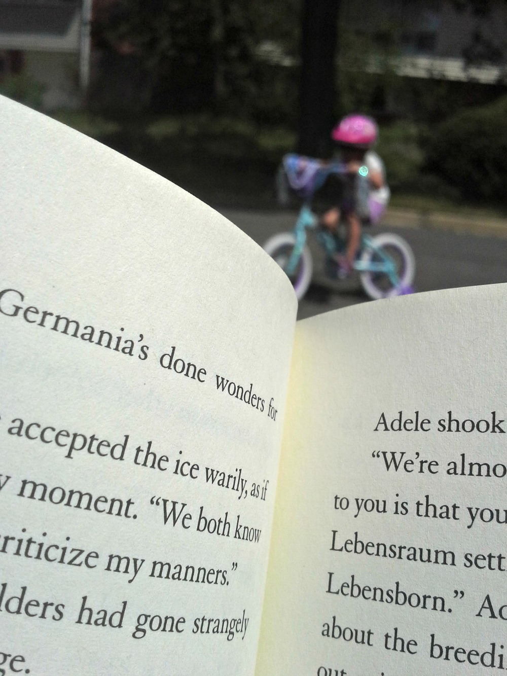 New bikes for the kids have given me a good excuse to sit on the curb while reading a book. (Pictured here: wolf by wolf by Ryan Graudin)