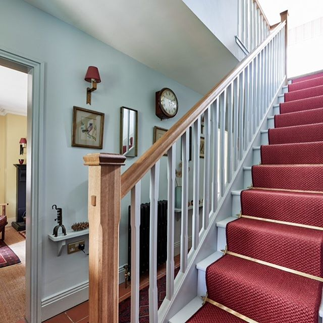 Entrance hall and stairs in Farrow and Ball skylight with warm red accents from the floor rugs and sisal stair runner #hallway #hallwaydecor #stairs #interior #interiors #interiorstyle #interiordesign #farrowandball #entrance #cottage #cottagestyle