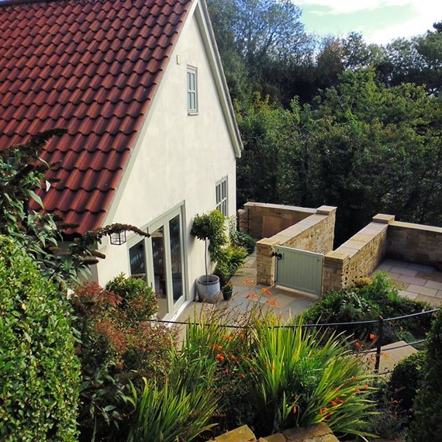 Side elevation of cottage from the hillside garden, sandstone walls create a smaller area of garden with patio and containers and small raised pond. #cottage #cottagegarden #garden #landscapedesign #flowers