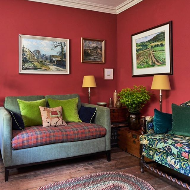 In this warm and cosy sitting room the walls are painted in Farrow and Ball Blazer Red. A mixture of colours and patterns and to the vibrancy of the room. #livingroom #livingroomdecor #interiordesign #interior #interiordecor #lounge #sofa #williammorris #abrahammoonfabrics  #cushion #colourful #cottage #cottagestyle #sofadotcom