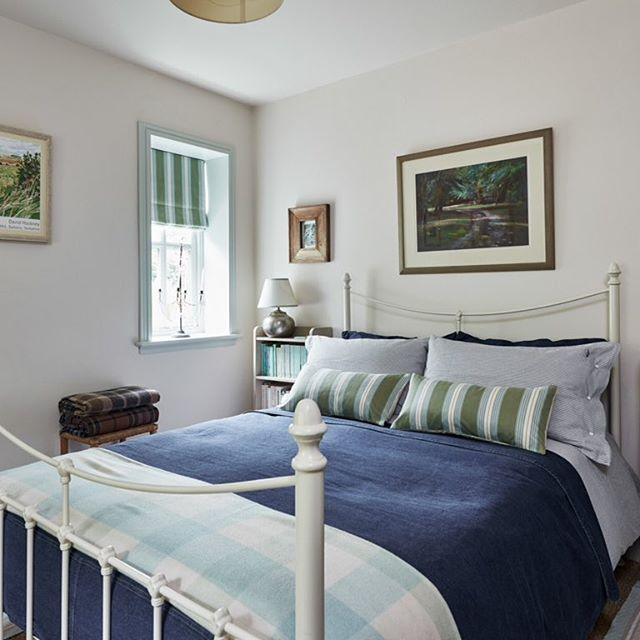 Costal inspired bedroom, denim bedcover , navy and white striped Oxford cotton bed linen from Lexington. Cashmere checked throw. Cushions and blinds in fabric from Ian Mankin. The walls are painted in Dimity and the window in Pale Powder by Farrow and Ball, giving the room a light and airy feel. #bedroomdecor #cottagestyle #coastalstyle #cottage #interiordecor #interior #interiors #beachhouse #ianmankin #bedlinen #lexingtoncompany